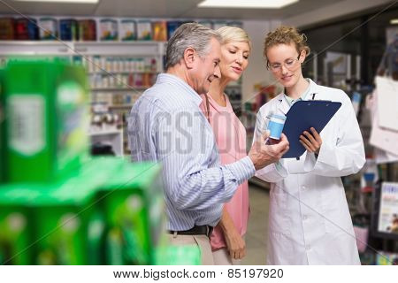 Pharmacist and her customers talking about medication in the pharmacy
