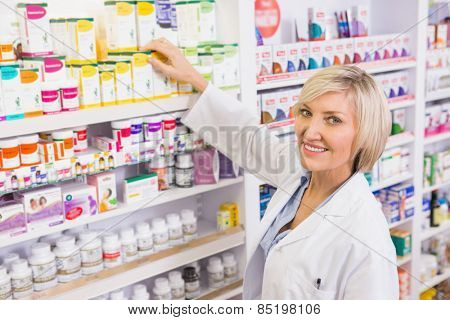 Smiling pharmacist taking box from shelf in the pharmacy