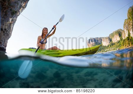 Young lady paddling the kayak in a bay with limestone mountains. Split shot with underwater view