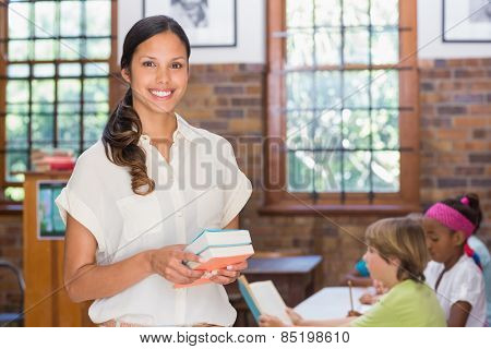 Pretty teacher smiling at camera in library at the elementary school