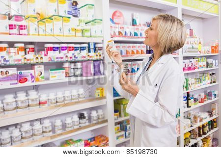 Smiling pharmacist holding prescription and medicine in the pharmacy