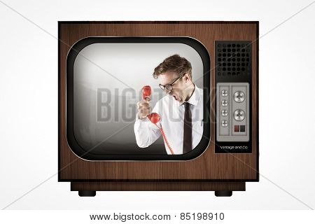 Angry geeky businessman holding telephone against retro tv