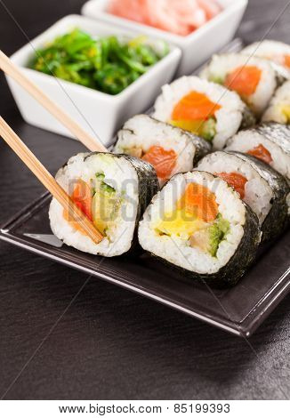 Delicious sushi rolls served on black plate and stone