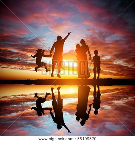 happy family on a background of the magnificent sunset over the sea