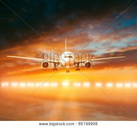 plane lands on the runway on a background of a magnificent sunset