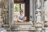 foto of krishna  - young happy child boy tourist meditating in angkor wat - JPG
