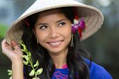 image of conic  - Pretty Vietnamese woman wearing a traditional conical hat with a flower in her hair smiling happily as she looks up into the air - JPG