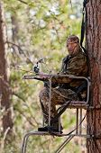 image of hunter  - Bow hunter in a ladder style tree stand  - JPG