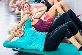 stock photo of senior men  - Group of senior people and young woman and men in fitness gym doing sit - JPG