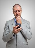 stock photo of scared  - Portrait of a scared man looking at his mobile phone - JPG