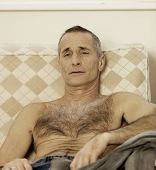 stock photo of lax  - Shirtless handsome man sitting on a sofa - JPG