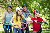stock photo of exercise bike  - Happy family on their bike at the park on a sunny day - JPG
