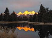 pic of mountain-range  - The mountains in the Grand Teton range are reflected in the still plaid waters of Schwabachers Landing in Wyoming on a fall morning at dawn - JPG