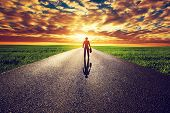 image of wander  - Man with suitcase and hat on long straight road towards sunset sky - JPG