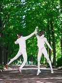 picture of rapier  - Two rapier fencer women fighting over park alley - JPG