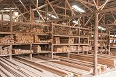 image of 2x4  - Wood stacked on shelving inside a lumber yard - JPG