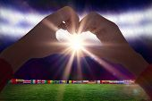 stock photo of football pitch  - Woman making heart shape with hands against football pitch with world cup flags - JPG