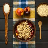 picture of crisps  - Overhead shot of a rustic bowl filled with baked plum and nectarine crumble or crisp with ingredients on the side photographed on dark wood with natural light - JPG