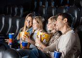 pic of movie theater  - Cheerful family having snacks while enjoying movie in cinema theater - JPG