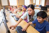 image of pupils  - Cute pupils in computer class with teacher at the elementary school - JPG