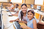 stock photo of pupils  - Cute pupils in computer class with teacher at the elementary school - JPG