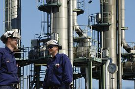 pic of refinery  - refinery workers with three fuel towers inside industry - JPG