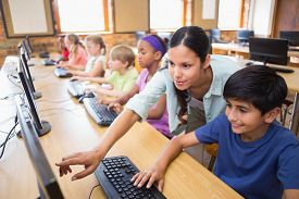 image of teachers  - Cute pupils in computer class with teacher at the elementary school - JPG