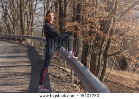 Woman Doing Stretching Before Jogging In Forest