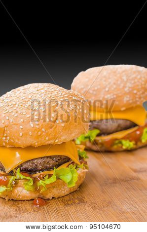 Two tasty cheeseburgers with lettuce; beef; double cheese and ketchup. Shallow focus.