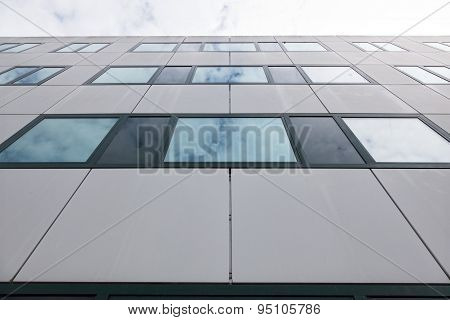 Modern Facade Of Office Buildings And Reflections Of Clouds In Windows