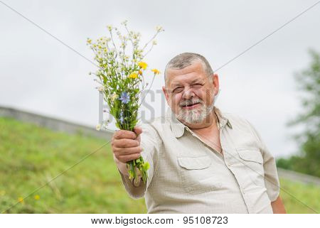 Outdoor portrait of a smiling senior man giving a bouquet
