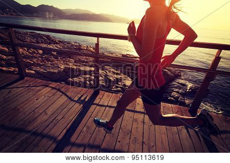 young fitness woman legs running on seaside wooden boardwalk