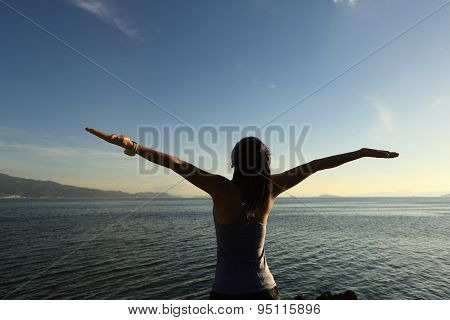 young cheering woman jogger open arms at sunrise seaside
