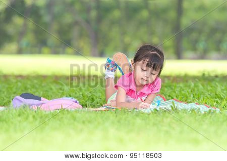 Asian Girl Outdoors Lying On The Grass And Drawing