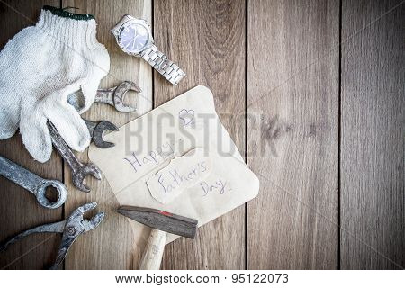 Happy Fathers Day With Top Border Of Tools And Ties On A Rustic Wood Background