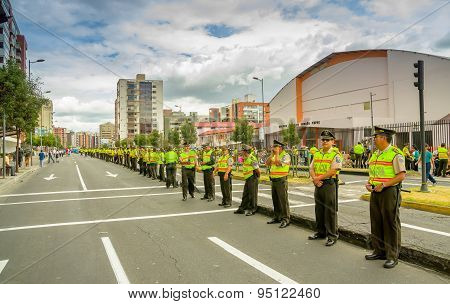 Long line police officers guarding the street as crowds await arrival of Pope Francis motorcade in r