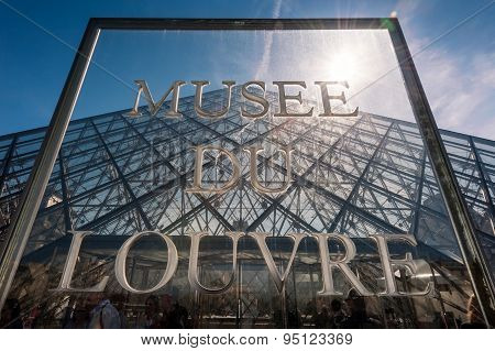 Musee Du Louvre Sign in front of The large glass pyramid at the Louvre Museum