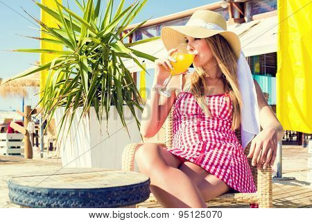 Young Woman Drinking A Orange Soda At A Beach Bar