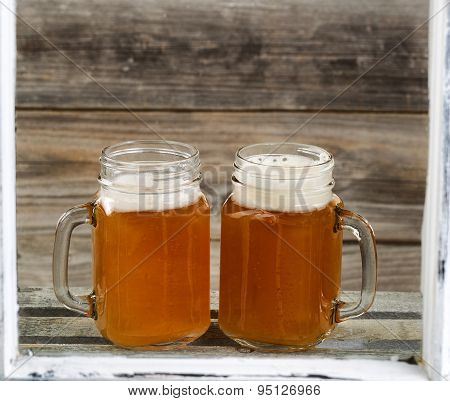 Window View Of Two Pints Of Fresh Cold Beer On Top Of Wooden Crate With Rustic Wood In Background