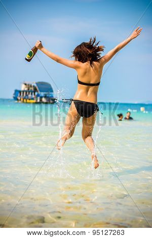Sexy Asian Thai Girl In Bikini Is Jumping With Joy On The Seashore Of Pattaya Sea With Alcohol Bottl