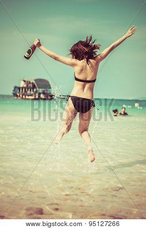 Sexy Asian Thai Girl In Bikini Is Jumping With Joy On The Seashore Of Pattaya Sea With Alcohol Bottl