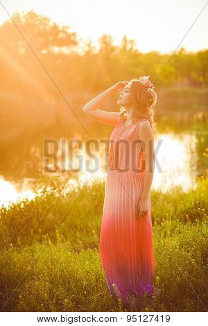 Young girl  at sunset by the river in the summer