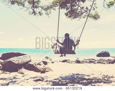 Young Man  In A Swing On Tropical Summer Beach