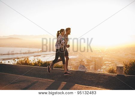 Young Couple Jogging On Hillside Road