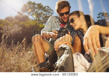 Couple On Hiking Trip Taking A Break Sitting And Looking At Pict