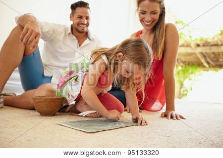 Family Sitting On Floor With Daughter Drawing