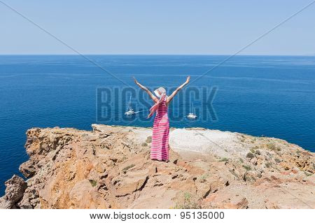 Woman In A Long Summer Dress Standing On A Cliff