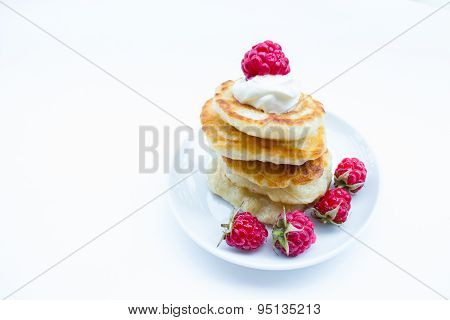 Stack of pancakes on plate  raspberries and sour cream, isolated