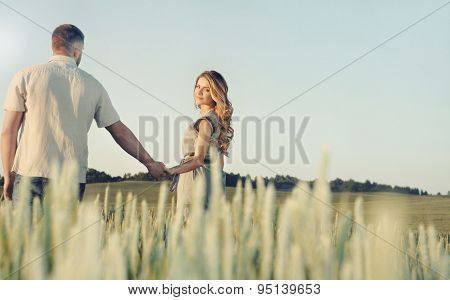 Stunning Sensual Young Couple In Love Posing In Summer Field Holding Hands