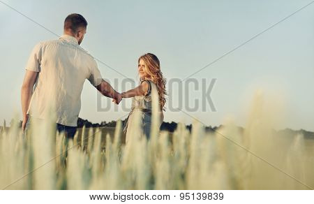 Stunning Happy Young Couple In Love Posing In Summer Field Holding Hands